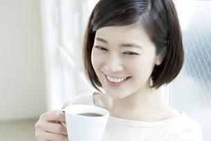 窓際でコーヒーを飲む20代女性の写真素材 [FYI01735283]