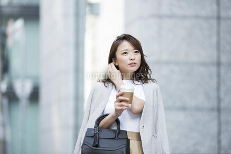 コーヒーを持つ若いビジネスウーマンの写真素材 [FYI01735285]