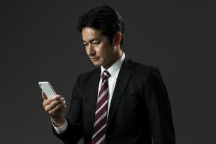 スマートフォンを見るビジネスマンの写真素材 [FYI01735295]