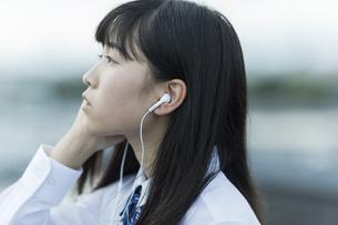 イヤホンで音楽を聴く女子学生の写真素材 [FYI01735349]