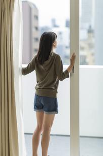 窓辺で外を眺める女の子の写真素材 [FYI01735354]