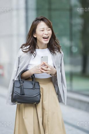 スマートフォンを持ち笑顔のビジネスウーマンの写真素材 [FYI01735404]
