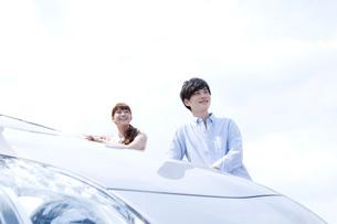 車のサイドに立つ20代カップルの写真素材 [FYI01735455]