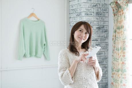 スマホを持つ笑顔の30代女性の写真素材 [FYI01735464]