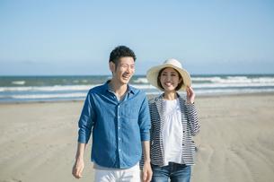 笑顔で砂浜を歩く20代30代カップルの写真素材 [FYI01735482]