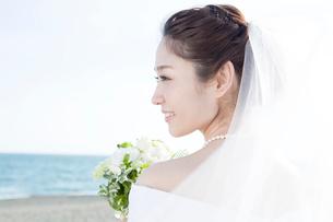 海辺に立つブーケを持つ花嫁の写真素材 [FYI01735498]