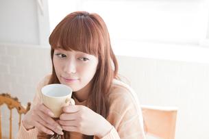 コーヒーカップを持つ若い女性の写真素材 [FYI01735543]