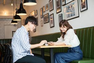 カフェでくつろぐ20代男女の写真素材 [FYI01735566]