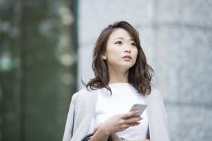 スマートフォンを持つビジネスウーマンの写真素材 [FYI01735579]