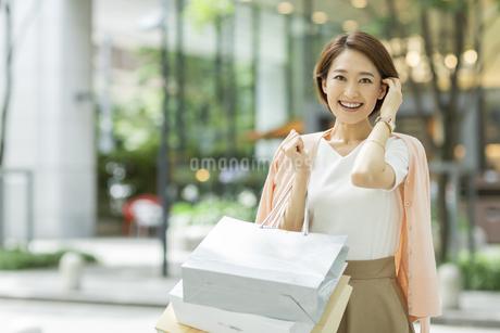 ショッピングバッグを持って微笑む女性の写真素材 [FYI01735583]