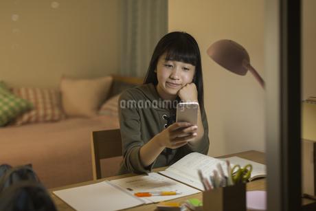 スマートフォンを見ながら勉強をする女の子の写真素材 [FYI01735646]