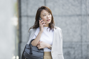 スマートフォンで通話をするビジネスウーマンの写真素材 [FYI01735658]