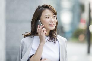 スマートフォンで通話をするビジネスウーマンの写真素材 [FYI01735671]