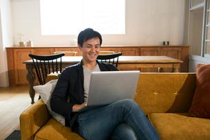 ソファに座りパソコンを操作する笑顔の30代男性の写真素材 [FYI01735707]