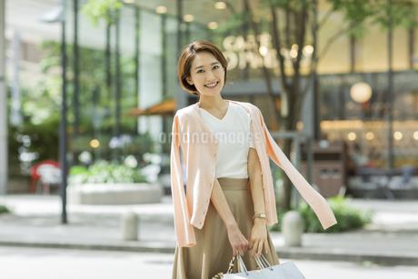 ショッピングバッグを持って微笑む女性の写真素材 [FYI01735722]