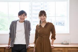 窓際に立つ笑顔の20代男女の写真素材 [FYI01735763]