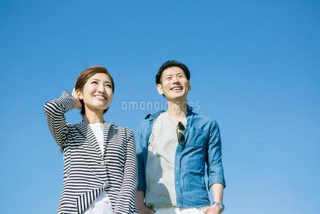 青空と爽やかな20代30代カップルの写真素材 [FYI01735770]