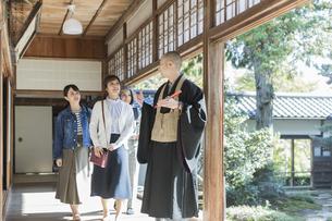 寺院を案内する住職と3人の女性の写真素材 [FYI01735864]
