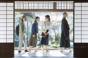 寺院を案内する住職と3人の女性の写真素材 [FYI01735869]