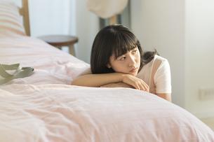 ベッドにもたれる女の子の写真素材 [FYI01735908]