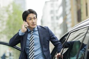 車から降りるビジネスマンの写真素材 [FYI01735954]