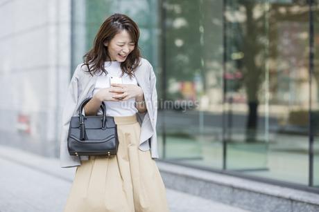 スマートフォンを持ち笑顔のビジネスウーマンの写真素材 [FYI01735968]
