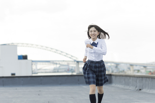 屋上で走る女子学生の写真素材 [FYI01735972]