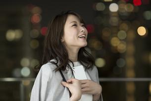 スマートフォンを持って笑顔のビジネスウーマンの写真素材 [FYI01736074]