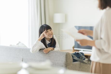 母親に成績表を見せる女の子の写真素材 [FYI01736082]