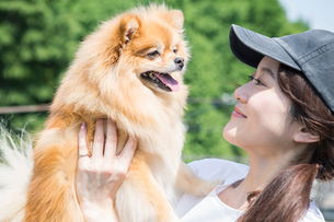屋外で犬を抱きかかえる笑顔の30代女性の写真素材 [FYI01736147]