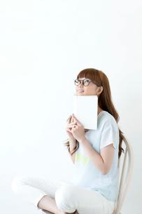 本を持ち見上げる若い女性の写真素材 [FYI01736167]