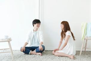 床に座ってくつろぐ20代カップルの写真素材 [FYI01736182]