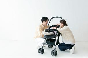 ベビーカーにいる赤ちゃんをあやす夫婦の写真素材 [FYI01736191]