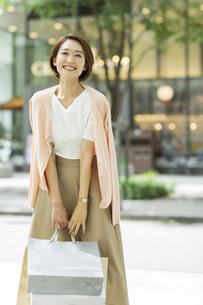 ショッピングバッグを持って微笑む女性の写真素材 [FYI01736213]