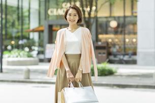 ショッピングバッグを持って微笑む女性の写真素材 [FYI01736343]