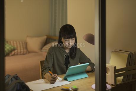 タブレットPCで勉強をする女の子の写真素材 [FYI01736348]