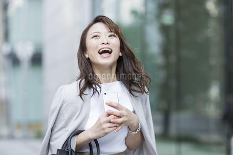 スマートフォンを持ち笑顔のビジネスウーマンの写真素材 [FYI01736409]