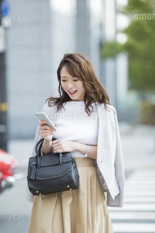 スマートフォンを操作するビジネスウーマンの写真素材 [FYI01736421]