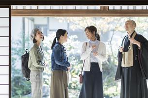 寺院を案内する住職と3人の女性の写真素材 [FYI01736433]