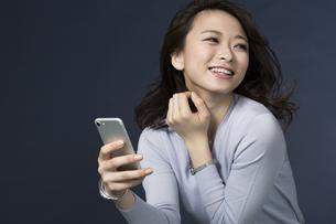 スマートフォンを持ち笑顔のビジネスウーマンの写真素材 [FYI01736442]
