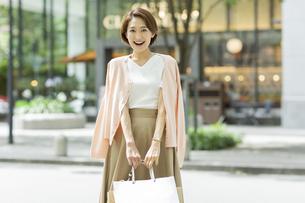 ショッピングバッグを持って微笑む女性の写真素材 [FYI01736471]