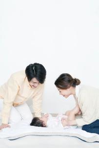 あおむけの赤ちゃんをと遊ぶ夫婦の写真素材 [FYI01736691]