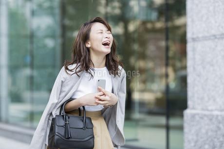 スマートフォンを持ち笑顔のビジネスウーマンの写真素材 [FYI01736702]