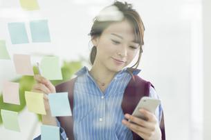 スマートフォンを操作するビジネスウーマンの写真素材 [FYI01736837]