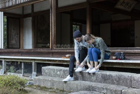 縁側に座り靴紐を結ぶ外国人の男女の写真素材 [FYI01736886]