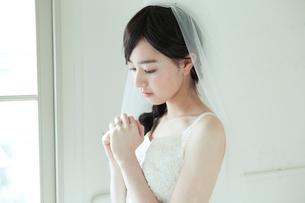 手を合わすウエディングドレス姿の20代女性の写真素材 [FYI01736904]