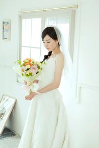 ブーケを持つウエディングドレス姿の20代女性の写真素材 [FYI01736920]