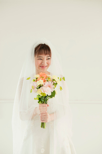 ブーケを持つウエディングドレス姿の笑顔の20代女性の写真素材 [FYI01736941]