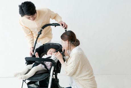 ベビーカーにいる赤ちゃんを見る夫婦の写真素材 [FYI01736956]