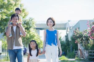 歩道を歩く笑顔の家族の写真素材 [FYI01736960]